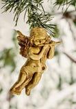 l'ange d'or accroche le jouet sur une branche neigeuse Photo libre de droits