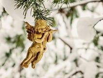 l'ange d'or accroche le jouet sur une branche neigeuse Photos libres de droits