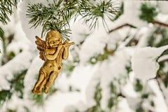 l'ange d'or accroche le jouet sur une branche neigeuse Images libres de droits