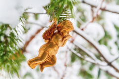 l'ange d'or accroche le jouet sur une branche neigeuse Image libre de droits