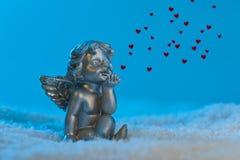 L'ange dans la configuration de neige affiche le coeur Photographie stock