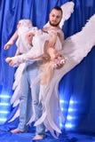 L'ange masculin enveloppe protectivement le compagnon féminin dans des ses ailes sur une haute de promontoire Image stock