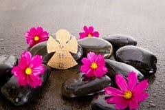 L'ange rose de fleurs et de toile de jute de cosmos forment sur la roche noire de massage Photographie stock libre de droits