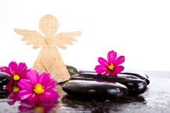 L'ange rose de fleurs et de toile de jute de cosmos forment sur la roche noire de massage Images libres de droits