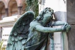 L'angelo afflitto che si inginocchia sulla tomba gira il suo sguardo fisso nella s fotografia stock libera da diritti