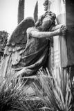 L'angelo afflitto che si inginocchia sulla tomba gira il suo sguardo fisso nella s fotografie stock
