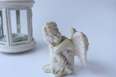 L'angelo d'annata bianco si siede su un fondo bianco fotografia stock