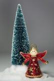 L'angelo rosso si leva in piedi davanti all'albero di Natale immagini stock libere da diritti