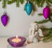 L'angelo sta considerando il fuoco della candela nell'ambito dei rami dell'abete Fotografie Stock