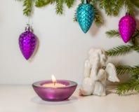 L'angelo sta considerando il fuoco della candela nell'ambito dei rami dell'abete Fotografia Stock
