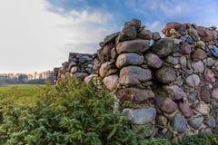 L'angle de la grange en pierre ruinée à une ferme abandonnée agricole Images libres de droits