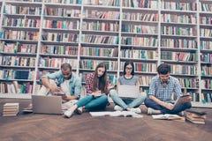 L'angle faible a tiré de quatre étudiants intelligents internationaux de rats de bibliothèque i photographie stock libre de droits