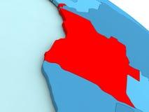 L'Angola en rouge sur le globe bleu Image stock
