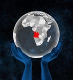 L'Angola sur le globe translucide dans des mains illustration de vecteur
