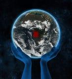 L'Angola sur terre de planète de nuit dans des mains illustration de vecteur