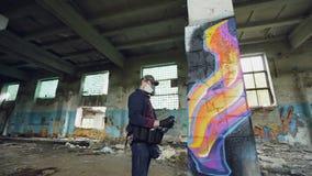 L'angolo basso sparato del giovane è graffito della pittura della maschera di protezione sulla colonna dentro fabbricato industri video d archivio