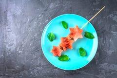 L'anguria sotto forma di stelle sugli spiedi con le foglie della menta si trova su un piatto blu Vista superiore Fotografia Stock