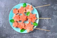 L'anguria sotto forma di stelle sugli spiedi con le foglie della menta si trova su un piatto Il piatto blu è come un razzo nello  Fotografia Stock