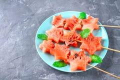 L'anguria sotto forma di stelle sugli spiedi con le foglie della menta si trova su un piatto Il piatto blu è come un razzo nello  Fotografie Stock Libere da Diritti