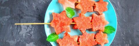 L'anguria sotto forma di stelle sugli spiedi con le foglie della menta si trova su un piatto Il piatto blu è come un razzo nello  Fotografie Stock