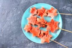 L'anguria sotto forma di stelle sugli spiedi si trova su un piatto Il piatto blu è come un razzo nello spazio Vista superiore Fotografie Stock