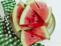 L'anguria succosa collega l'antiossidante dell'estate della parte di un tovagliolo del piatto su un fondo di legno bianco immagine stock