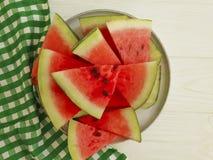 L'anguria succosa collega l'antiossidante della parte di un tovagliolo del piatto su un fondo di legno bianco immagini stock libere da diritti