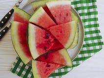 L'anguria succosa collega l'antiossidante naturale dell'estate della parte di un tovagliolo del piatto su un fondo di legno bianc fotografia stock libera da diritti