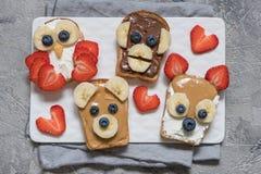 L'animal drôle fait face à des pains grillés avec la banane, la fraise et la myrtille Photos stock