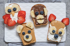 L'animal drôle fait face à des pains grillés avec la banane, la fraise et la myrtille Photo stock