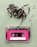 L'annata che sembra la cassetta di nastro magnetico per l'audio registrazione di musica con la nota di canzone spegne Fotografia Stock