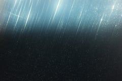 L'annata di scintillio accende il fondo blu scuro leggero ed oro defocused Fotografia Stock