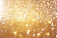 L'annata di scintillio accende il fondo oro leggero ed il nero defocused Fotografia Stock Libera da Diritti