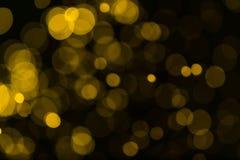 L'annata di scintillio accende il fondo oro scuro ed il nero defocuse Fotografie Stock Libere da Diritti