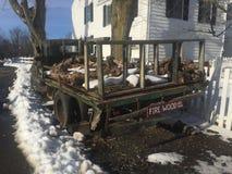 L'annata ha arrugginito camion con neve come supporto della legna da ardere accanto alla fattoria Immagine Stock