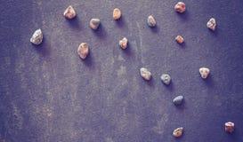 L'annata ha filtrato le pietre sul fondo scuro dell'ardesia di lerciume Fotografia Stock