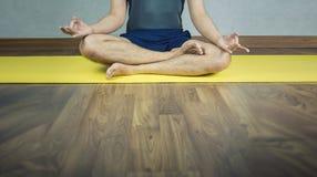 L'annata ha filtrato sull'uomo che fa la posa di yoga, posizione di loto sulla stuoia fotografie stock
