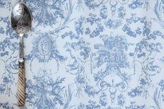 L'annata ha inciso il cucchiaio su un fondo di carta blu-chiaro fotografia stock