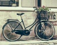 L'annata ha stilizzato la foto dei fiori di trasporto della vecchia bicicletta immagine stock libera da diritti