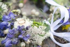 L'anneau de mariage avec un diamant se trouve sur un bouquet de mariage des fleurs sauvages Photos stock