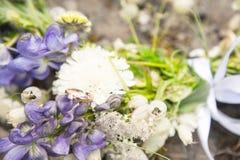 L'anneau de mariage avec un diamant se trouve sur un bouquet de mariage des fleurs sauvages Images stock