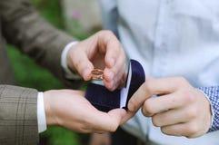 L'anneau de mariage se situe dans des mains au marié Image stock