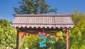 L'anniversaire monte en ballon bleu et blanc en parc de ville Alcôve avec le numéro de deux - deux années anniversaires Image libre de droits