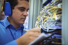 L'annotazione di mantenimento del tecnico dello scaffale ha montato il server sulla lavagna per appunti Fotografia Stock Libera da Diritti