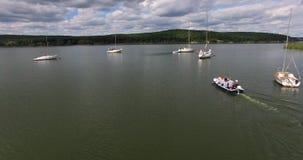L'antenna segue la barca a bassa quota Fuco che sorvola l'imbarcazione a motore con la gente stock footage