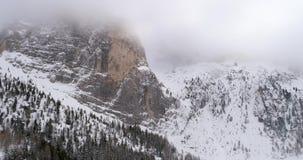 L'antenne arrière avec la forêt neigeuse de montagne et en bois chez Sella passent l'inclinaison vers le bas Mauvais temps brumeu clips vidéos