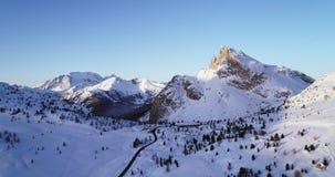 L'antenne en avant à la vallée neigeuse avec la forêt en bois et la route au falzarego passent Coucher du soleil ou lever de sole banque de vidéos