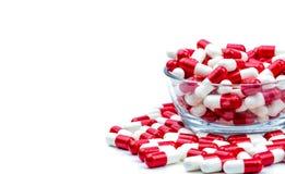 L'antibiotique rouge et blanc capsule des pilules dans le bol en verre Photo stock