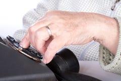 L'anziana della mano compone il numero del telefono Fotografia Stock