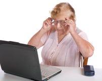 L'anziana in vetri esamina il taccuino dello schermo Fotografie Stock Libere da Diritti